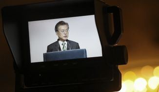 """South Korea's President Moon Jae-in is seen on a video screen as he delivers his speech entitled """"ROK and ASEAN: Partners for Achieving Peace and Co-prosperity in East Asia"""" during the 42nd Singapore Lecture organized by the Institute of South East Asian Studies (ISEAS) in Singapore, Friday, July 13, 2018. (AP Photo/Yong Teck Lim)"""