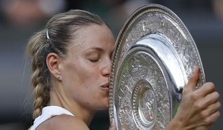 Angelique Kerber of Germany kisses the trophy after defeating Serena Williams of the US in the women's singles final match at the Wimbledon Tennis Championships, in London, Saturday July 14, 2018. (Andrew Couldridge, Pool via AP)