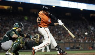 San Francisco Giants' Buster Posey drives in a run with a single during the sixth inning against the Oakland Athletics in a baseball game Friday, July 13, 2018, in San Francisco. (AP Photo/Marcio Jose Sanchez)