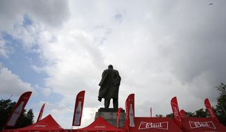In this July 11, 2018 photo, booths marketing products by event sponsors Budweiser and Coca-Cola stand beside a statue of Lenin, as fans arrive for the semifinal match between Croatia and England at Luzhniki Stadium, during the 2018 soccer World Cup in Moscow, Russia. AP Photo/Rebecca Blackwell)