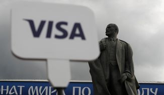 In this July 11, 2018 photo, a man holds up a Visa sign in front of a statue of Lenin, as fans arrive for the semifinal match between Croatia and England at Luzhniki Stadium, during the 2018 soccer World Cup in Moscow, Russia. AP Photo/Rebecca Blackwell)
