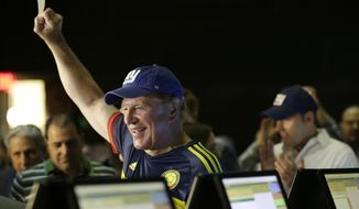 Former New Jersey Sen. Raymond Lesniak holds up a ticket after he casted the very first bet at the Meadowlands Racetrack, Saturday, July 14, 2018, in East Rutherford, N.J. Meadowlands Racetrack is the fourth sports betting outlet in New Jersey following the state's U.S. Supreme Court victory in a case that cleared the way for all 50 states to legalize sports betting. (AP Photo/Julio Cortez)