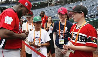 World Team manager David Ortiz, left, signs autographs for young fans before the All-Star Futures baseball game, Sunday, July 15, 2018, at Nationals Park, in Washington. The the 89th MLB baseball All-Star Game will be played Tuesday. (AP Photo/Alex Brandon)