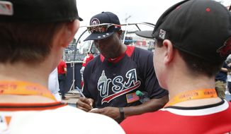 U.S. Team Manager Torii Hunter, center, signs autographs for young fans ahead of the All-Star Futures baseball game, Sunday, July 15, 2018, at Nationals Park, in Washington. The the 89th MLB baseball All-Star Game will be played Tuesday. (AP Photo/Alex Brandon)