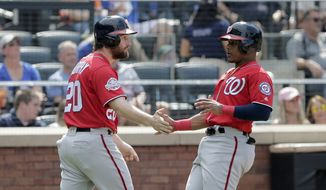 Washington Nationals' Daniel Murphy, left and Wilmer Difo celebrate after scoring on a single hit by Trea Turner during the seventh inning of the baseball game against the New York Mets at Citi Field, Sunday, July 15, 2018, in New York. (AP Photo/Seth Wenig)