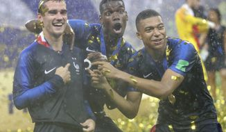 France's Antoine Griezmann, points to two stars on his jersey indicating two world cup wins, as he celebrates with Paul Pogba and Kylian Mbappe after the final match between France and Croatia at the 2018 soccer World Cup in the Luzhniki Stadium in Moscow, Russia, Sunday, July 15, 2018. France won the final 4-2. (AP Photo/Matthias Schrader)