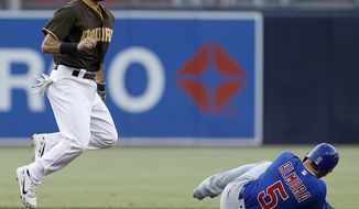 San Diego Padres second baseman Carlos Asuaje, left, leaps away after forcing out Chicago Cubs' Albert Almora Jr., then throwing to first to get Kris Bryant at first for a double play during the first inning of a baseball game in San Diego, Friday, July 13, 2018. (AP Photo/Alex Gallardo)