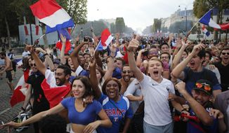 People celebrate on the Champs Elysees avenue after France won the soccer World Cup final match between France and Croatia, Sunday, July 15, 2018 in Paris. France won its second World Cup title by beating Croatia 4-2 . (AP Photo/Francois Mori)