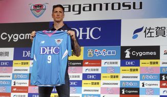 Fernando Torres poses with his uniform of Sagan Tosu during a press conference in Tokyo Sunday, July 15, 2018. Former Spain striker Torres signed to play for Sagan Tosu in the J1 League last week. (AP Photo/Eugene Hoshiko)