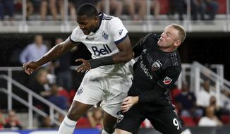 Vancouver Whitecaps defender Doneil Henry, left, and D.C. United forward Wayne Rooney (9) compete for a header during the second half of an MLS soccer match at Audi Field, Saturday, July 14, 2018, in Washington. (AP Photo/Alex Brandon)