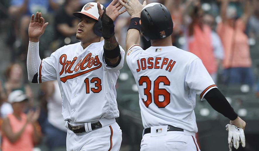 Baltimore Orioles' Manny Machado, left, and Caleb Joseph score against the Texas Rangers in the third inning of a baseball game, Sunday, July 15, 2018, in Baltimore. (AP Photo/Gail Burton)