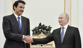 Russian President Vladimir Putin, right, shake hands with the Emir of Qatar Sheikh Tamim bin Hamad al-Thani during their meeting in the Kremlin in Moscow, Russia, Sunday, July 15, 2018. (Yuri Kadobnov/Pool Photo via AP)