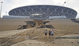 Three men look at a major landslip on an embankment after a heavy rain next to the Volgograd Arena, one of Russia's World Cup venues in Volgograd, Russia, Sunday, July 15, 2018. The stadium, built on the banks of the Volga River, held four World Cup games and cost an estimated $275 million. (AP Photo/Ilya Varlamov)