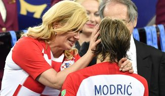 Croatian President Kolinda Grabar-Kitarovic hugs Croatia's Luka Modric after France won the final match between France and Croatia at the 2018 soccer World Cup in the Luzhniki Stadium in Moscow, Russia, Sunday, July 15, 2018. (AP Photo/Martin Meissner)