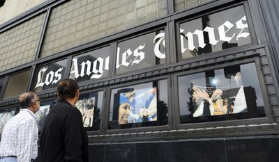 FILE - In this May 16, 2016, file photo, pedestrians look at news photos posted outside the Los Angeles Times building in downtown Los Angeles. The Los Angeles Times reports that biotech billionaire Dr. Patrick Soon-Shion officially takes control of the storied newspaper and the San Diego Union-Tribune on Monday, June 18, 2018. Soon-Shiong is spending $500 million for the two news organizations, Spanish-language Hoy and some community newspapers from Chicago-based Tronc. The Times once had more than 1,200 journalists and more than 25 foreign bureaus. Now it employs about 400 journalists. (AP Photo/Richard Vogel, File)