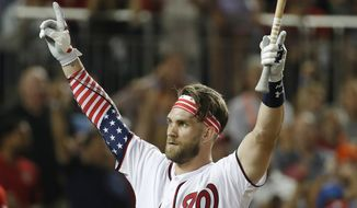 Washington Nationals Bryce Harper (34) signals to the crowd as he walks back to the dugout during the MLB Home Run Derby, at Nationals Park, Monday, July 16, 2018 in Washington. The 89th MLB baseball All-Star Game will be played Tuesday. (AP Photo/Alex Brandon)