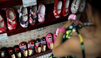 In this July 13, 2018, photo, a child selects shoes as Chinese-made shoes carrying a Chinese map and U.S. flags are on display for sale at a shop in Beijing. China announced it filled a World Trade Organization challenge Monday to U.S. President Donald Trump's proposal for a tariff hike on $200 billion of Chinese goods, reacting swiftly amid deepening concern about the economic impact of their spiraling technology dispute. (AP Photo/Andy Wong)