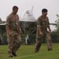 British military soldiers walk past a scale model of a F35 jet forming part of an exhibit on the grounds of the Celtic Manor Resort prior to a NATO summit in Newport, Wales on Wednesday, Sept. 3, 2014. NATO heads of state meet for a two-day summit beginning on Thursday. (AP Photo/Jon Super)