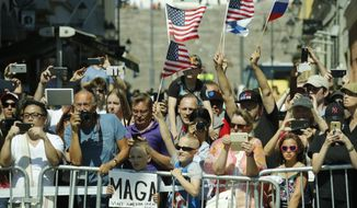 Bystanders waves American and Russian flags when watching the motorcade of U.S. President Donald Trump on his way to the Presidential Palace in Helsinki, Finland, for a meeting with Russian President Vladimir Putin Monday, July 16, 2018. (AP Photo/Pablo Martinez Monsivais)