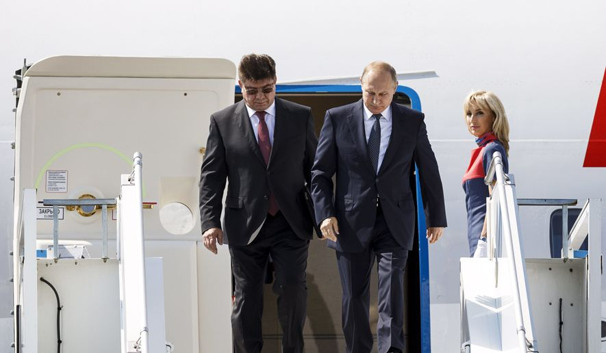 Russia's new ambassador to Finland Pavel Kuznetsov, left, escorts Russian President Vladimir Putin as he disembarks the plane at Helsinki airport in Vantaa, Finland, Monday, July 16, 2018. Putin arrived for his summit with U.S. President Donald Trump. (Ronni Rekomaa/Lehtikuva via AP)