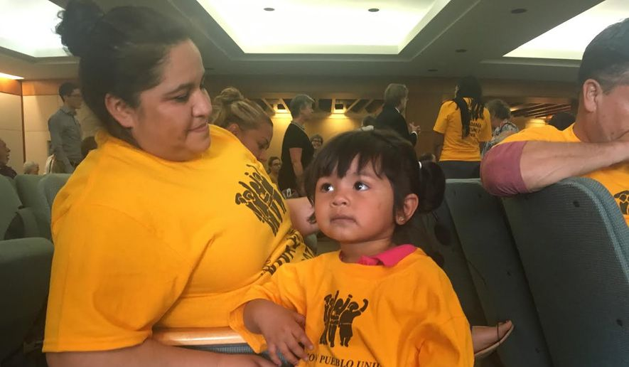 Two-year-old Amanda Ordonez, center, and her baby sitter, Veronica Velazquez await the start of a hearing in Santa Fe, N.M., where lawmakers heard testimony about conditions inside federal detention facilities in the state, Monday, July 16, 2018. (AP Photo/Mary Hudetz)