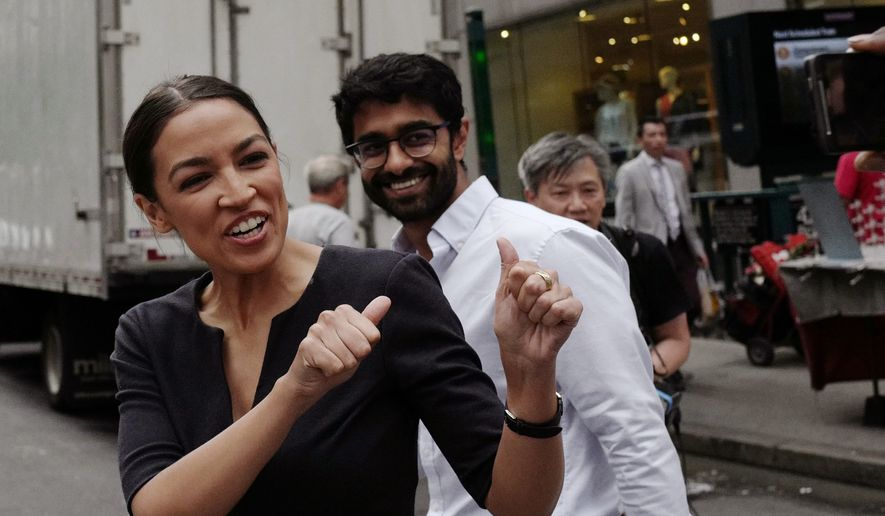 In this Wednesday June 27, 2018, file photo, Alexandria Ocasio-Cortez, left, the winner of New York's Democratic Congressional primary, greets supporters following her victory, along with Saikat Chakrabarti, founder of Justice Democrats and senior adviser for her campaign.  Ocasio-Cortez is back on the campaign trail, but this time in the Midwest. The 28-year-old Democratic rising star is stumping for two young, progressive Democrats hoping to win Democratic primaries in Kansas and Michigan. (AP Photo/Mark Lennihan, File)