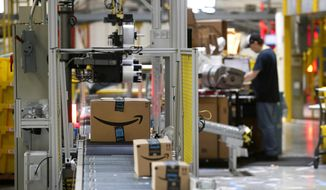 FILE- In this Aug. 3, 2017, file photo, packages pass through a scanner at an Amazon fulfillment center in Baltimore. Amazon's Prime Day starts July 16, 2018, and will be six hours longer than last year's and will launch new products. (Photo/Patrick Semansky, File)