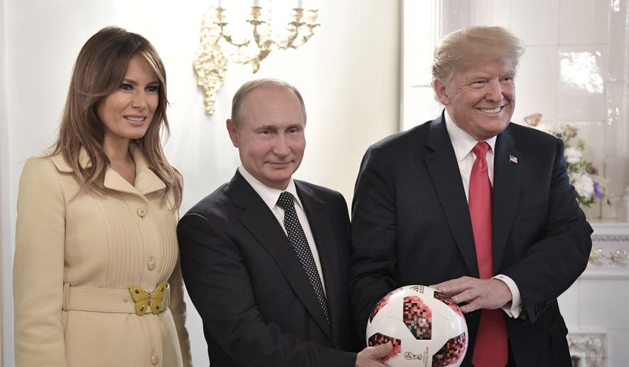 U.S. First Lady Melania Trump, left, Russian President Vladimir Putin, center, and U.S. President Donald Trump, pose with a soccer ball after a press conference following their meeting at the Presidential Palace in Helsinki, Finland, Monday, July 16, 2018. (Alexei Nikolsky, Sputnik, Kremlin Pool Photo via AP)