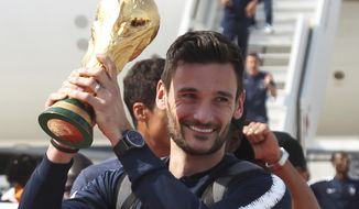 French goalkeeper and captain Hugo Lloris holds the cup as the French soccer team arrives at Charles de Gaulle airport, Monday, July 16, 2018 in Roissy, north of Paris. France prepares to welcome home the national soccer team for a victory lap down the grand Champs-Elysees avenue, where hundreds of thousands thronged after the team's 4-2 victory Sunday over Croatia to capture the soccer World Cup. (AP Photo/Bob Edme)