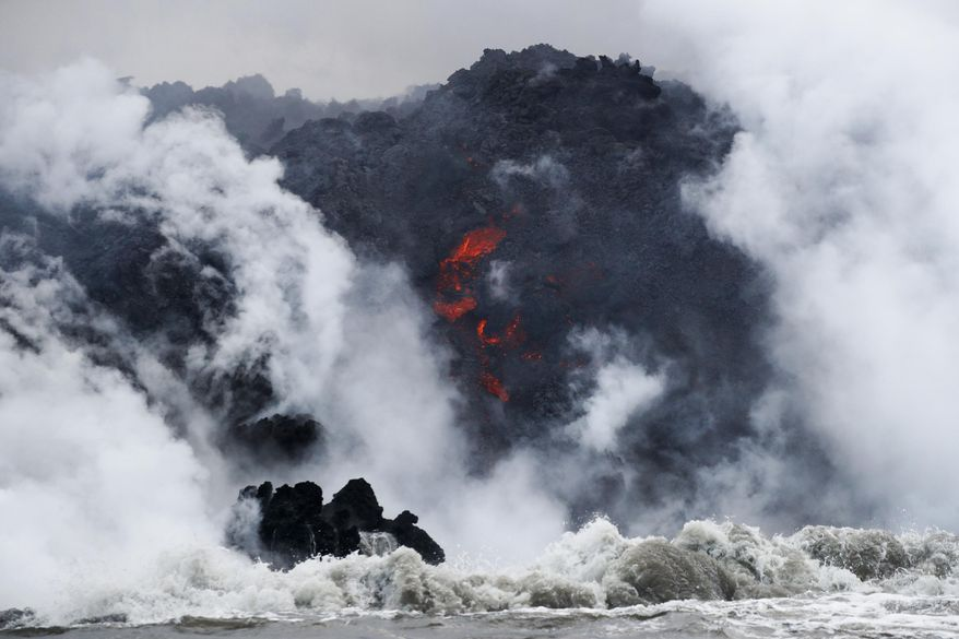 FILE - In this May 20, 2018 file photo, lava flows into the ocean near Pahoa, Hawaii. Officials say an explosion sent lava flying through the roof of a tour boat off the Big Island, Monday, July 16, 2018, injuring at least 13 people. The people were aboard a tour boat that takes visitors to see lava from an erupting volcano plunge into the ocean. (AP Photo/Jae C. Hong, File)