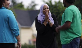 Attorney Tahirah Amatul-Wadud, who is challenging incumbent U.S. Rep. Richard Neal, D-Mass., center, talks with Dondre Scott, right, during a visit to a community garden while campaigning in the Mason Square neighborhood of Springfield, Mass. Monday, June 18, 2018. At left is Ivette Hernandez, who is running for Mass. House of Representatives. (AP Photo/Charles Krupa)