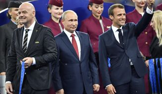 FIFA President Gianni Infantino, Russian President Vladimir Putin and French President Emmanuel Macron, from left, wait on the podium after the final match between France and Croatia at the 2018 soccer World Cup in the Luzhniki Stadium in Moscow, Russia, Sunday, July 15, 2018. (AP Photo/Martin Meissner)