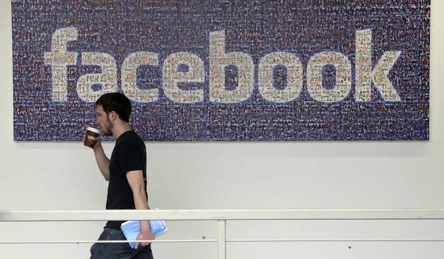 In this March 15, 2013, file photo, a Facebook employee walks past a sign at Facebook headquarters in Menlo Park, Calif. The San Jose Mercury News reports Saturday, March 17, 2018 that building permits compiled by Buildzoom show Facebook plans to erect the 465,000 square-foot (43,200 square-meter) building at its campus in Menlo Park, Calif. (AP Photo/Jeff Chiu, File)