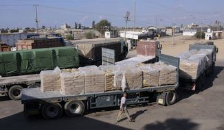 In this Tuesday, Oct. 14, 2014, file photo, a Palestinian worker walks next to trucks loaded with sacks of cement at the Kerem Shalom border crossing on its way from Israel to Rafah in the southern Gaza Strip. Israel shut down the cargo crossing of Kerem Shalom with the Gaza Strip on Tuesday in response to continued Hamas hostilities, even after it agreed to a cease-fire ending 24 hours of intense fighting. (AP Photo/Eyad Baba, File)