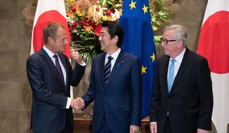 Japanese Prime Minister Shinzo Abe, center, shakes hands with European Council President Donald Tusk next to European Commission President Jean-Claude Juncker, right, before a meeting at Abe's official residence in Tokyo Tuesday, July 17, 2018. The European Union and Japan are signing a widespread trade deal Tuesday that will eliminate nearly all tariffs, seemingly defying the worries about trade tensions set off by U.S. President Donald Trump's policies. (Martin Bureau/Pool Photo via AP)