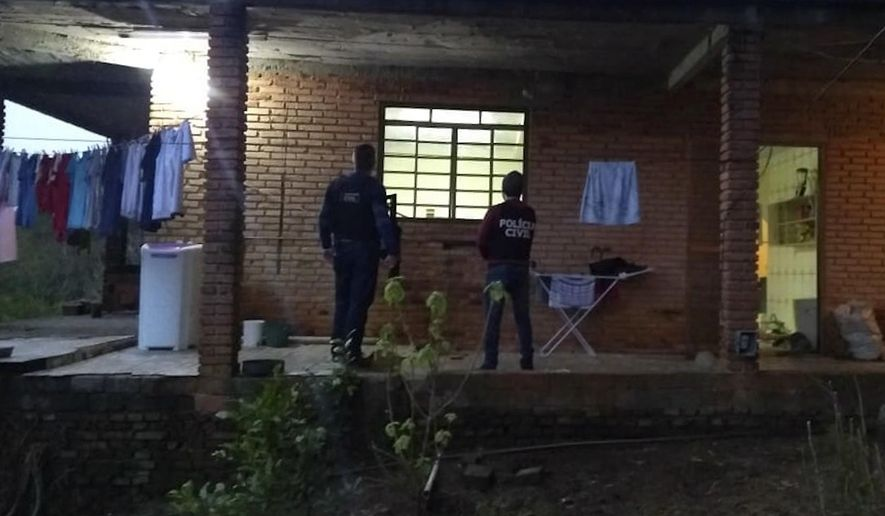 In this photo released by the Brazilian Civil Police, officers stand on the porch of a house where the mother of Brazil's soccer player Taison was rescued, in Monte Bonito rural area, Rio Grande do Sul state, Brazil, Monday, July 16, 2018. Taison's mother was kidnapped a day prior when she unknowingly opened a door for criminals who came to her house with a bouquet of flowers. (AP Photo/Brazilian Civil Police)