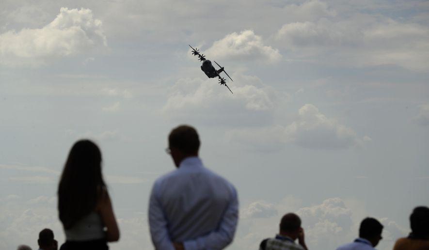 Spectators watch an Airbus 400M take part in a flying display at the Farnborough Airshow in Farnborough, England, Monday, July 16, 2018. (AP Photo/Matt Dunham)