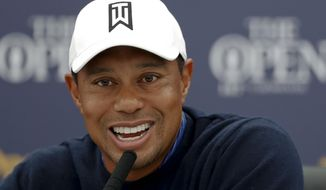 Tiger Woods of the United States smiles as he answers a question at a press conference for the 147th British Open Golf championships in Carnoustie, Scotland, Tuesday, July 17, 2018. The Opens Golf championships start Thursday. (AP Photo/Alastair Grant)