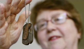 ADVANCE FOR USE SATURDAY, JULY 21 - In this July 10, 2018 photo, Mary Beth Seiser holds her father's dog tags at her home in West Bend, Wis. Seiser's father, Franklin H. Schwamb, served with the United States Army beginning in 1946. She believes the tags were lost in 1946 when he was training at Camp Hale in Colorado. The tags were found by Jason Homola in Colorado by a metal detector. The tags were turned over to the organization, Purple Hearts Returned. Michael Brennan with the organization returned the tags to Seiser on Memorial Day weekend in West Bend. (John R. Ehlke/West Bend Daily News via AP)