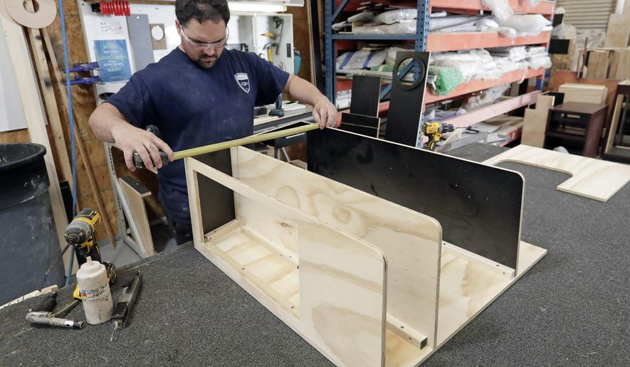 FILE- In this July 11, 2018, file photo a worker assembles interior cabinets for a boat at Regal Marine Industries in Orlando, Fla. On Tuesday, July 17, the Federal Reserve reports on U.S. industrial production for June. (AP Photo/John Raoux, File)