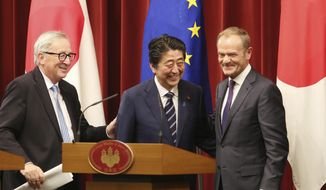 Japanese Prime Minister Shinzo Abe, center, European Commission President Jean-Claude Juncker, left, and European Council President Donald Tusk, right, smile after their joint press conference of Japan-EU summit at Abe's official residence in Tokyo Tuesday, July 17, 2018. (AP Photo/Koji Sasahara, Pool)