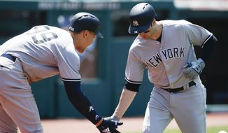 New York Yankees' Neil Walker celebrates with Aaron Judge (99) after hitting a solo home run off Cleveland Indians starting pitcher Trevor Bauer during the fourth inning of a baseball game, Sunday, July 15, 2018, in Cleveland. (AP Photo/Ron Schwane)
