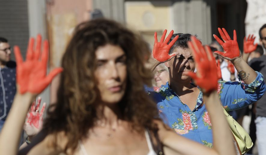 People with hands painted in red protest in front of the Italian Interior Ministry headquarters in Rome, Wednesday, July 18, 2018. Dozens of protesters marched in front of the ministry to protest government's hard-line immigration policy. (AP Photo/Alessandra Tarantino)