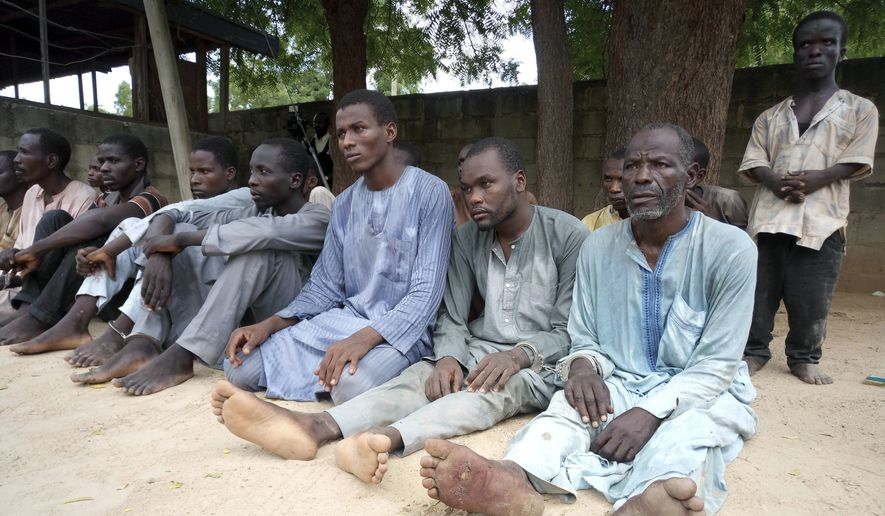 A group of men identified by Nigerian police as Boko Haram extremist fighters and leaders are shown to the media, in Maiduguri, Nigeria, Wednesday, July 18, 2018. A Nigerian police official says authorities have arrested 22 Boko Haram extremist leaders and members who are responsible for the kidnappings in Chibok and more than 50 suicide bombings. (AP Photo/Jossy Ola) ** FILE **