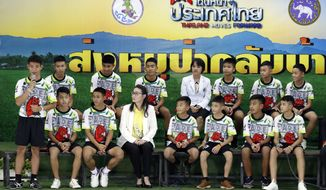 """Coach"""" Ake"""" Ekkapol Janthawong, left, speaks on behalf of the 12 boys and himself and their cave rescue during a press conference discussing their ordeal in Chiang Rai, northern Thailand, Wednesday, July 18, 2018. The 12 boys and their soccer coach rescued after being trapped in a flooded cave in northern Thailand are recovering well and are eager to eat their favorite comfort foods after their expected discharge from a hospital soon. (AP Photo/Vincent Thian)"""
