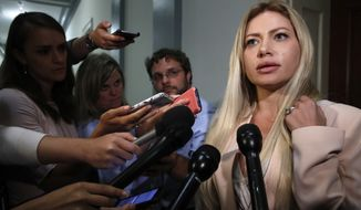 Simona Mangiante Papadopoulos, wife of former Donald Trump campaign adviser George Papadopoulos, speaks to members of the media after attending a closed-door meeting with Democrats on the House intelligence committee, Wednesday, July 18, 2018, on Capitol Hill in Washington. George Papadopoulos pleaded guilty last year to lying to investigators about his contacts with people linked to Russia during the campaign. (AP Photo/Jacquelyn Martin)