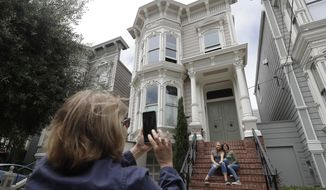 "Aries Layton, seated left, and her aunt Kelsy Layton pose as Debra Layton, Aries' grandmother and Kelsy's mother, foreground, takes photos outside a Victorian home made famous by the television show ""Full House"" in San Francisco, Tuesday, July 17, 2018. Tour buses will no longer be swinging by the San Francisco house made famous in the popular 1990s sitcom ""Full House."" The San Francisco Municipal Transportation Agency voted Tuesday to ban commercial vehicles from Broderick Street after neighbors complained.  (AP Photo/Jeff Chiu)"