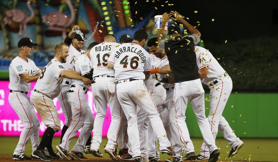 FILE - In this July 11, 2018, file photo, Miami Marlins' Starlin Castro is mobbed by teammates after he hit a walk-off single in the 12th inning of a baseball game against the Milwaukee Brewers, in Miami. The Marlins won 5-4. Just look at the standings: Thanks to a recent surge, the young Marlins (41-57) are not even last in the NL East. And opponents rave. (AP Photo/Wilfredo Lee, File)