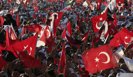 FILE - In this Sunday, July 9, 2017 file photo, supporters of Kemal Kilicdaroglu, the leader of Turkey's main opposition Republican People's Party, hold Turkish flags in Istanbul, as they gather for a rally following their 425-kilometer (265-mile) 'March for Justice' from capital Ankara to Istanbul. Turkey declared a three-month state of emergency after a failed coup attempt in 2016, and has extended it seven times since then, but it is scheduled to end at midnight Wednesday July 18, 2018, though opposition leaders insists that new anti-terrorism laws are just as oppressive as the emergency powers they will replace. (AP Photo/Lefteris Pitarakis, File)