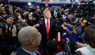 Surrounded by the press, then-candidate Donald Trump grins following the fifth GOP presidential debate, staged in Las Vegas in 2015. (ASSOCIATED PRESS)